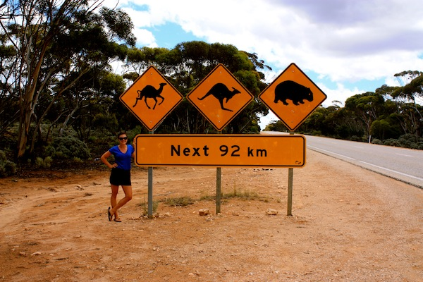 Christine Amorose at camel, kangaroo, wombat road sign on the Nullarbor, Australia