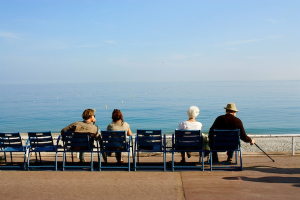 A young couple and an old couple stare at the sea, Nice, France