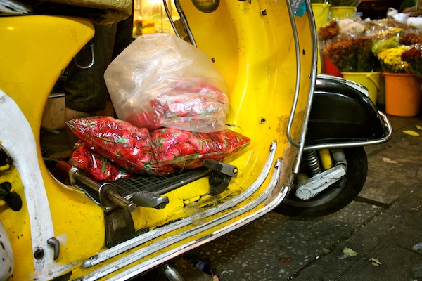 Bag of pink blooms on a yellow Vespa at 24-hour Bangkok Flower Market, Thailand