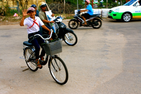 Boy waves hello on bike in Pho Quoc, island in South Vietnam