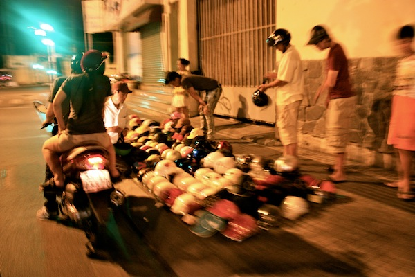 Man selling motorbike helmuts on street on Saigon After Dark tour with Vietnam Vespa Adventures