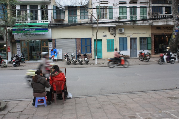 Women sitting on side of street as motorcycle roars by in Hanoi, Vietnam