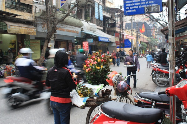 Woman selling flowers on bicycle on street in Hanoi, Vietnam