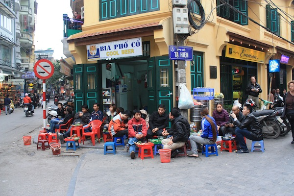 Men drinking fresh beer on the corner on kiddie furniture in Hanoi, Vietnam
