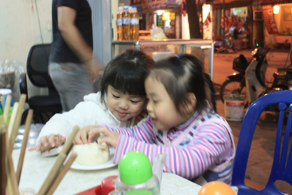Little girls eating a steamed pork bun in Hanoi, Vietnam