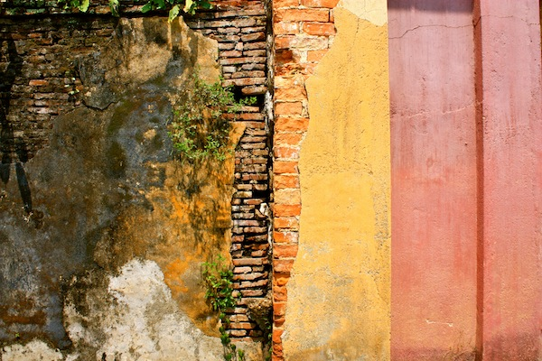 Exposed brick, peeling paint and weeds in a wall at Hue Imperial City Citadel, Vietnam