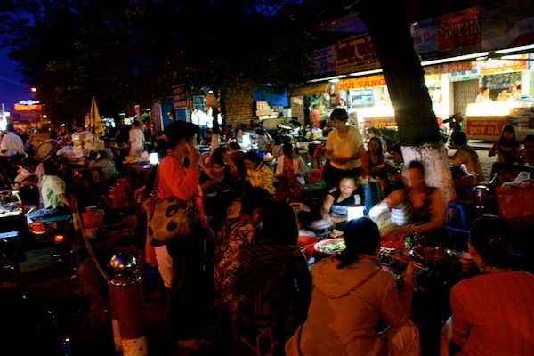 Women cooking and eating at night market in Hue, Vietnam