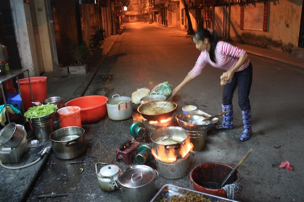 Woman cooking in alley before sunrise in Hanoi, Vietnam