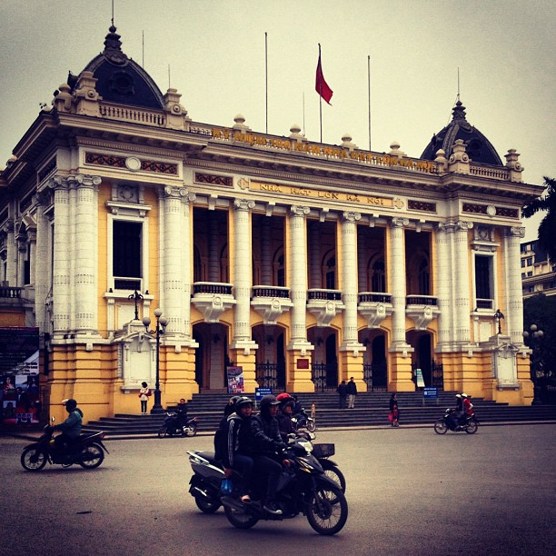 Opera House with motorbikes rushing by in Hanoi, Vietnam