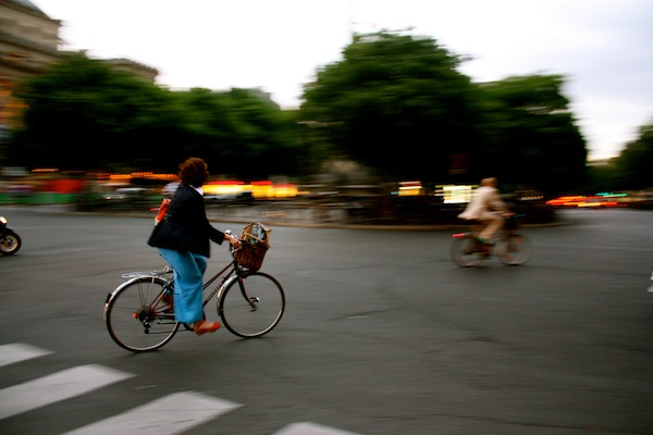 Chic French woman on a bicycle at Chatelet in Paris, France