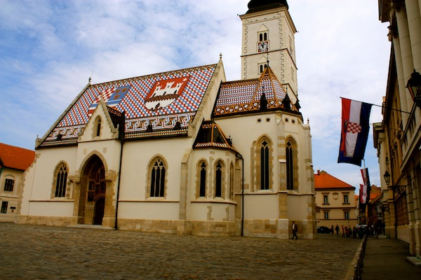 Croatian tile roof St Mark's church and flags in square in Zagreb, Croatia