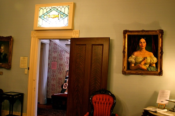 Interior of Cannonball House with clasped hands stained glass and portrait of Eugenia