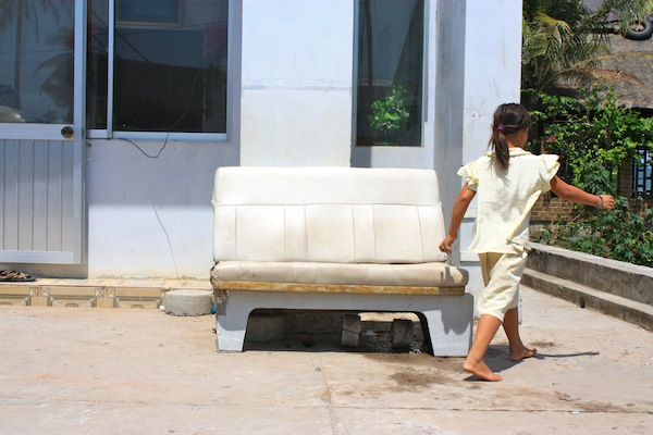 Girl in white walks by white couch in Cay Sao, Phu Quoc Island, Vietnam