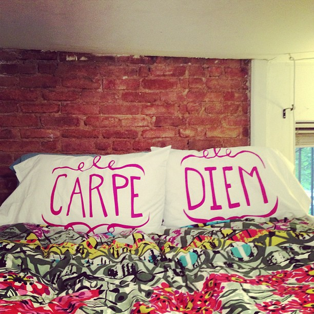 Carpe Diem pillowcases and flowered loft bedding with exposed brick wall