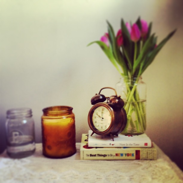 Alarm clock, Voluspa candle and fresh tulips on a nightstand