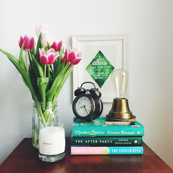 Le Labo candle and flowers on a nightstand